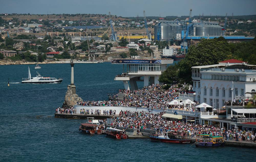 People on the riverfront overlooking the Bay of Sevastopol in Sevastopol watch aircraft performing demonstration flights