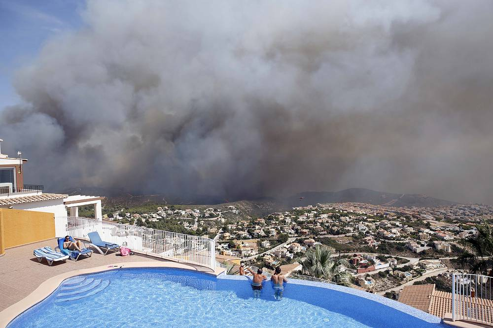 Two men look at a wildfire from a swimming pool as it burns nearby Benitachel village, eastern Spain, September 5