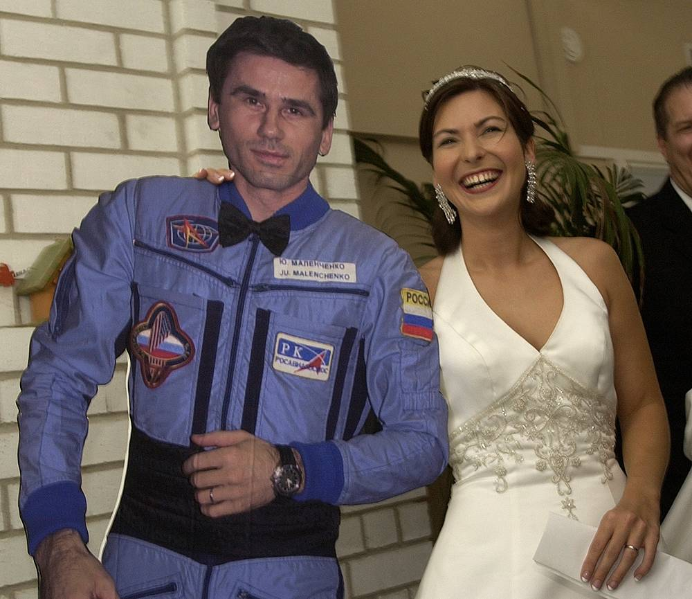 Ekaterina Dmitriev Malenchenko with a cardboard cutout of her new husband, cosmonaut Yuri Malenchenko, following a long distance wedding ceremony between the couple, 2003, in Houston