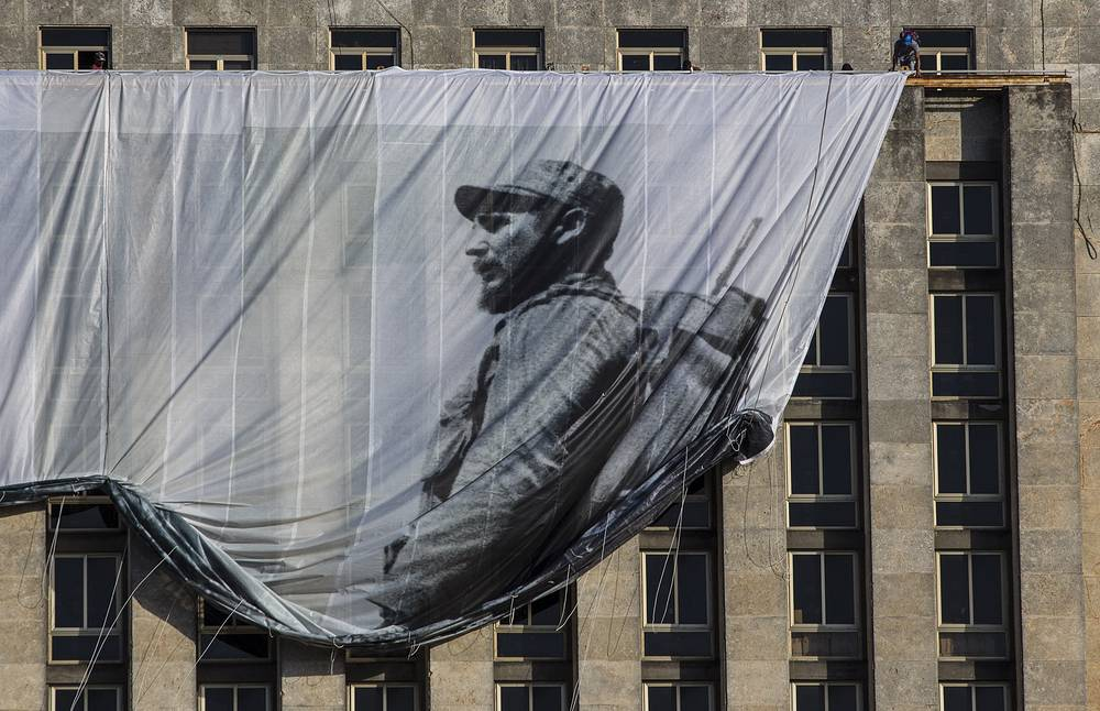 Men hang a giant banner with a picture of Fidel Castro as a young revolutionary, from the Cuban National Library building in Havana, Cuba