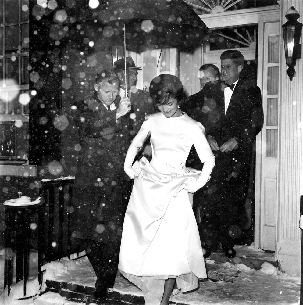 Jacqueline Kennedy in her inaugural ball gown and her husband, President-elect John F. Kennedy leaving their home en route to the inaugural concert in Washington, 1961