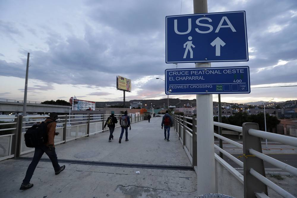 People make their way towards the border crossing in Tijuana, Mexico