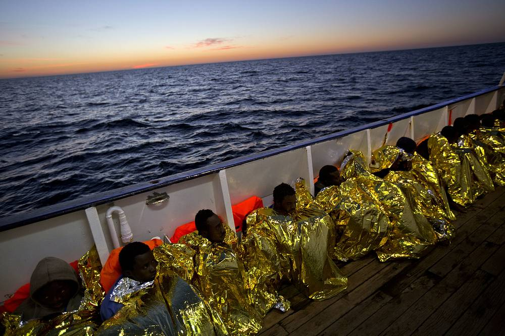 Sub-Saharan migrants sit on the deck of the Golfo Azzurro boat after been rescued from a rubber boat by members of Proactive Open Arms NGO, in the Mediterranean sea, Libya, January 27