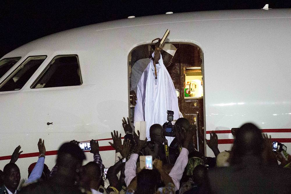 Gambia's defeated leader Yahya Jammeh waves to supporters as he departs from Banjul airport, January 21