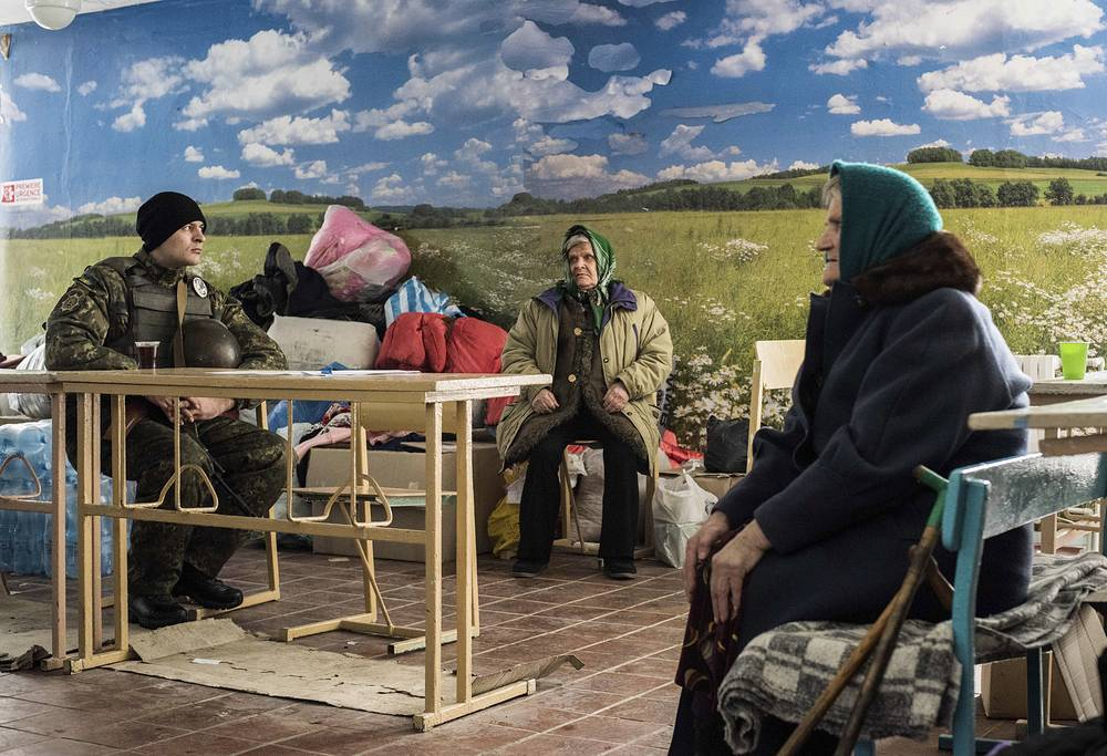 A Ukrainian soldier guards as two elderly women wait to get a humanitarian aid in Avdeyevka, eastern Ukraine, February 5