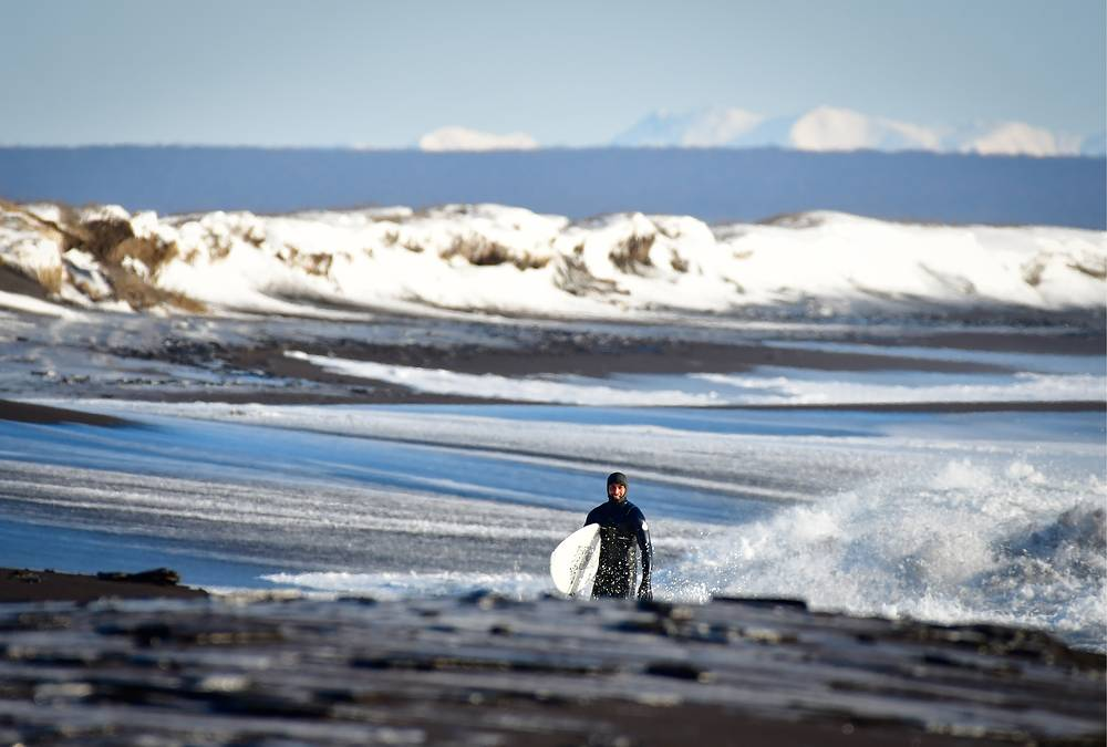 A surfer on the Avachinsky Bay coast, Russia,  February 26