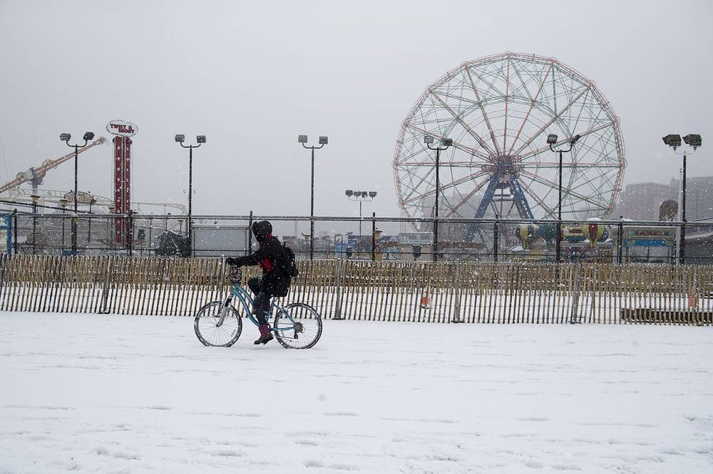 A woman rides a bike during a snow storm on the Coney Island boardwalk in New York