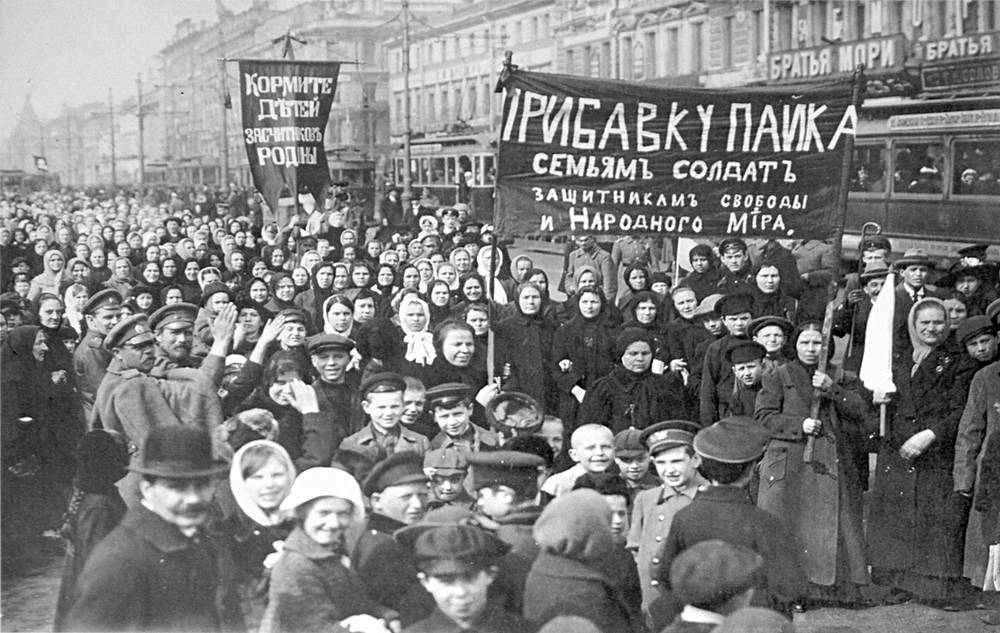 "A demonstration of workers from the Putilov plant in Petrograd. The left banner reads ""Feed the children of the defenders of the motherland""; the right banner, ""Increase payments to the soldiers' families - defenders of freedom and world peace"",  March 1917"