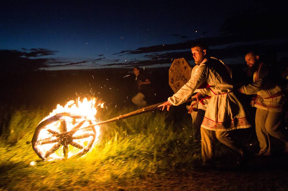 Participants roll a lit wheel during the Solstice ethnic festival in the village of Okunevo, Russia, June 22