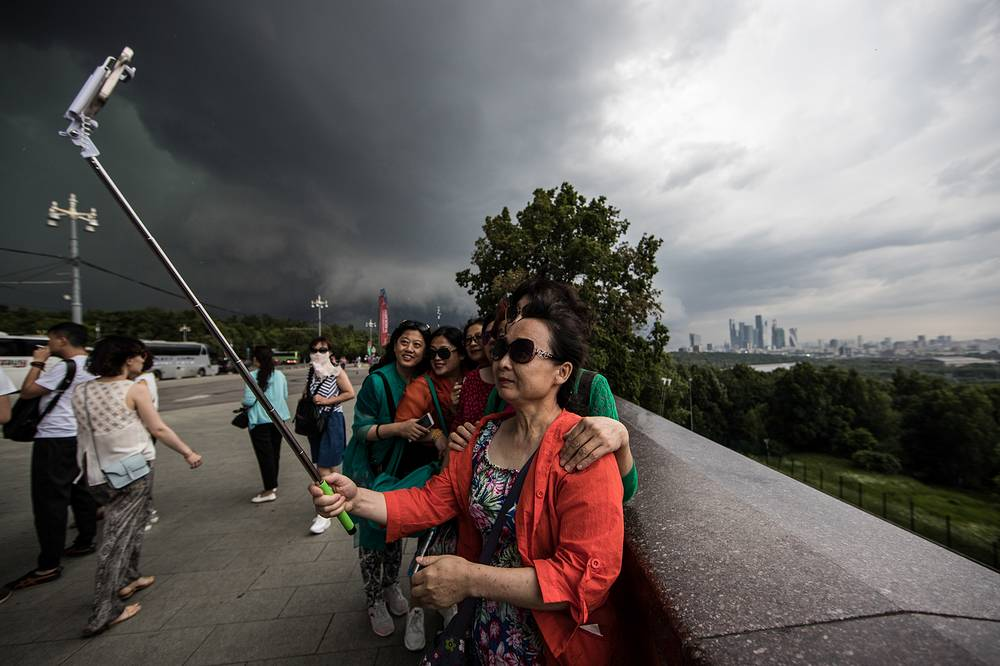 Tourists take selfie during a storm on Moscow's Sparrow Hills