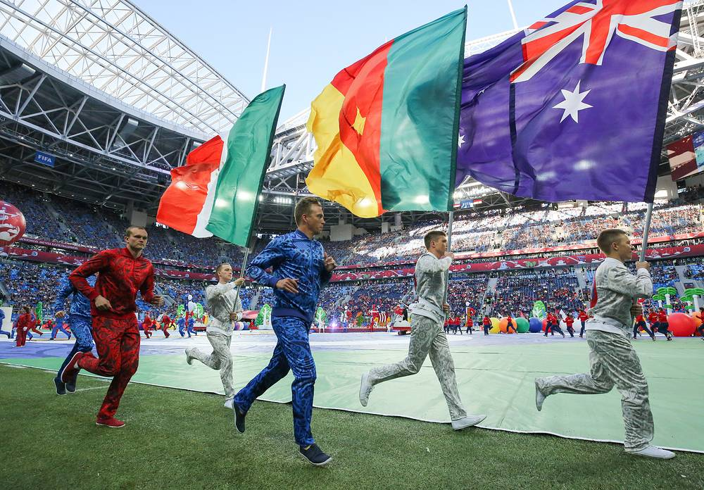 Performers carry the national flags of Mexico, Cameroon, and Australia