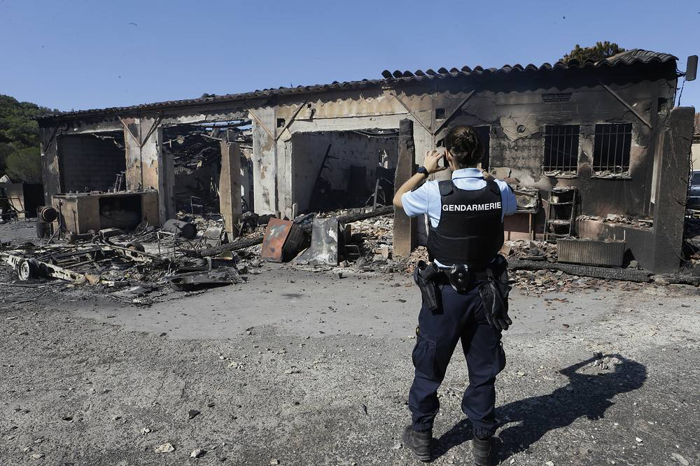 A gendarme takes snapshots of the charred remains of burnt caravans and camper vans at a warehouse in La Londe-les-Maures, France