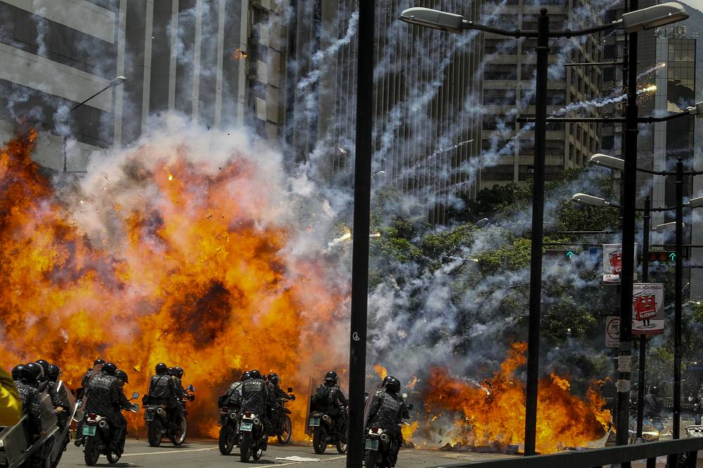 An explosion in the street near motorized police in the vicinity of the Altamira Square, in Caracas, Venezuela, July 30