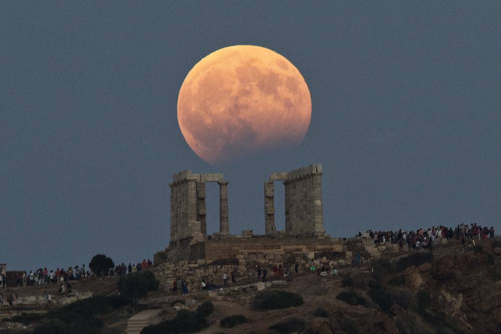 Full moon rises above the 5th Century BC Temple of Poseidon at Cape Sounio, south of Athens, Greece