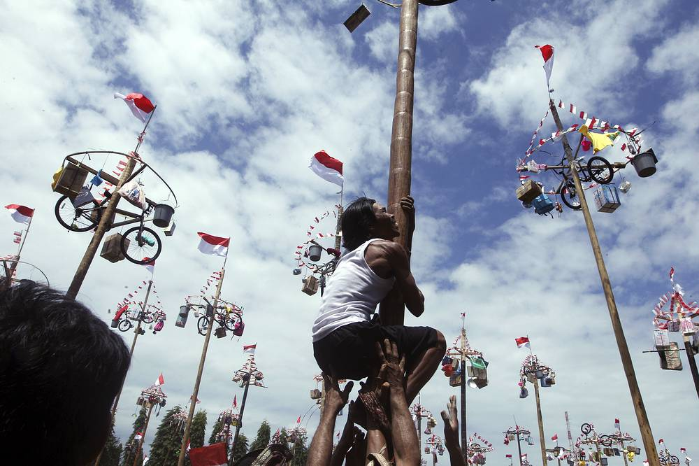A man tries to climb a greased pole to retrieve prizes such as a bicycle as part of the Independence Day festivities in Bali, Indonesia, August 17