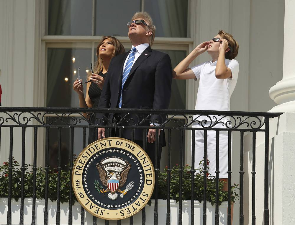 US President Donald Trump, first lady Melania Trump and their son Barron watch the solar eclipse at the White House in Washington