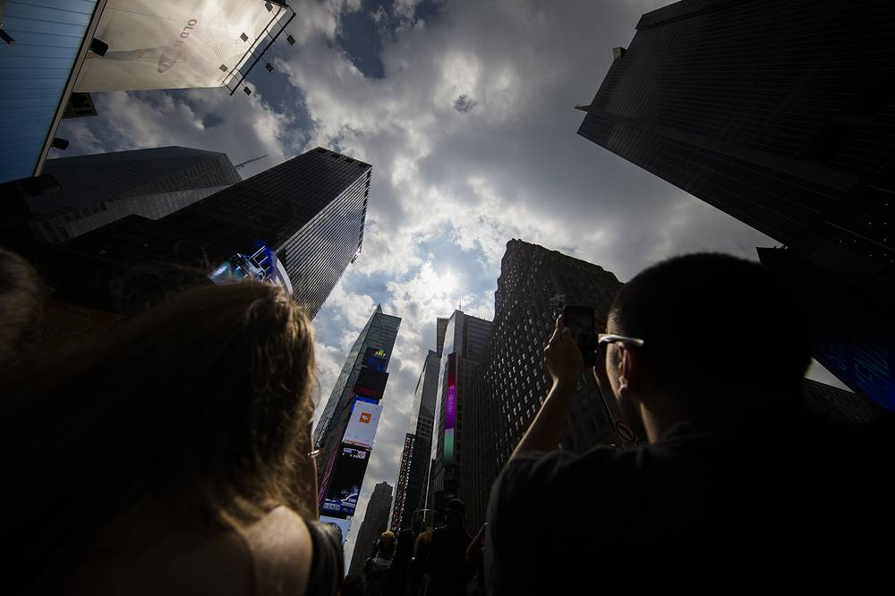 Onlookers take photos and look through special glasses to view a partial solar eclipse in New York