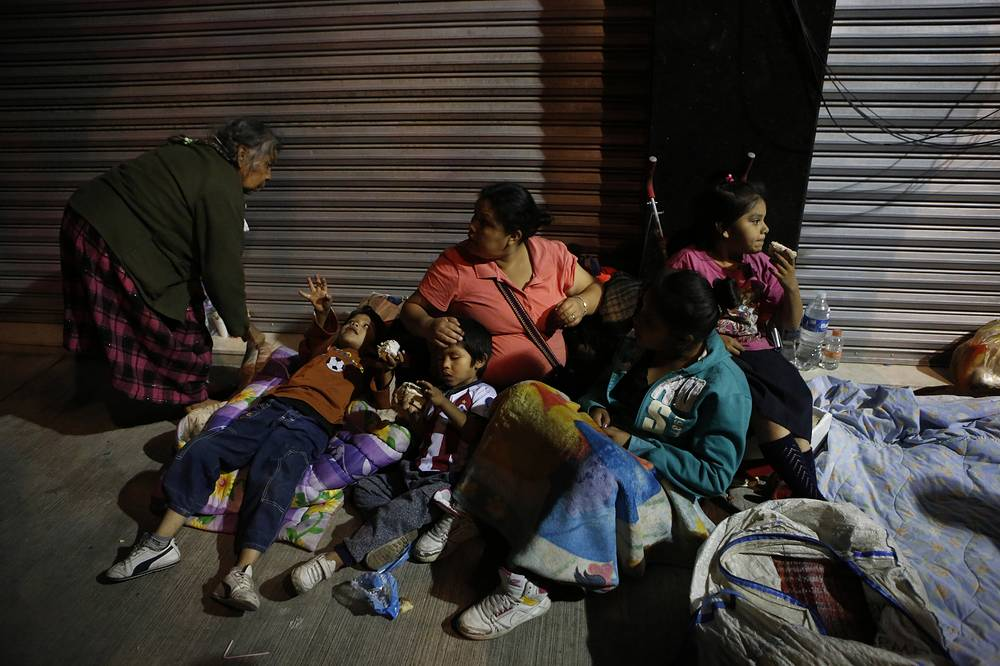 Families fearing aftershocks prepare to sleep on the street in the Roma neighborhood of Mexico City