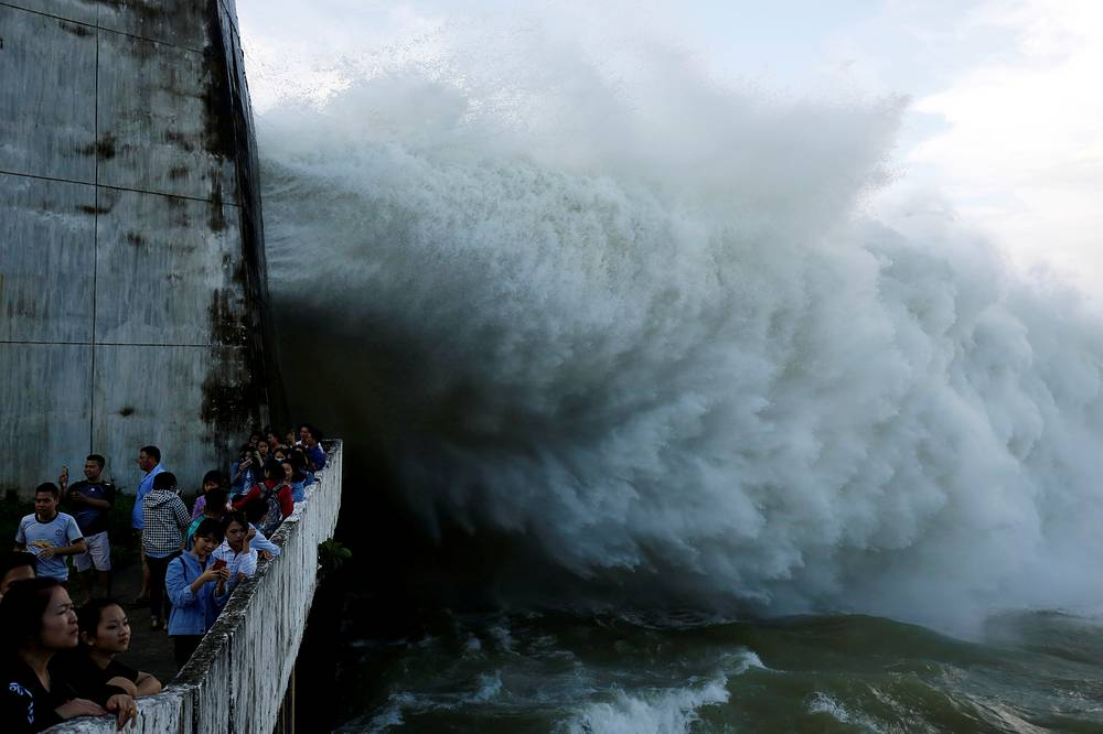 People watch as Hoa Binh hydroelectric power plant opens the flood gates after a heavy rainfall caused by a tropical depression in Hoa Binh province, outside Hanoi, Vietnam, October 12