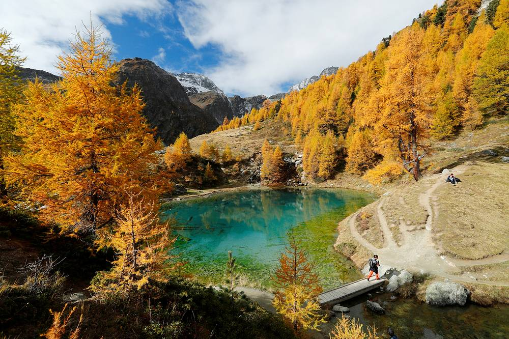 Hikers enjoy a warm autumn day near the Lac Bleu near Arolla in the Val d'Herens, Switzerland, October 12
