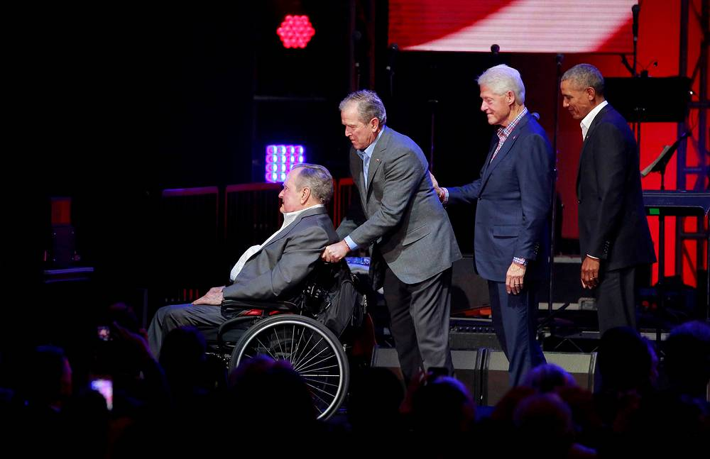 Former US President George H.W. Bush is helped off the stage by George W. Bush as Bill Clinton and Barack Obama follow close behind during a concert at Texas A&M University where the five former US Presidents including Jimmy Carter attended a concert benefiting hurricane relief efforts in College Station, Texas, US, October 21