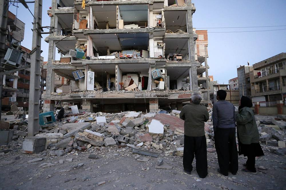 People look at destroyed buildings after an earthquake at the city of Sarpol-e-Zahab in western Iran, November 13