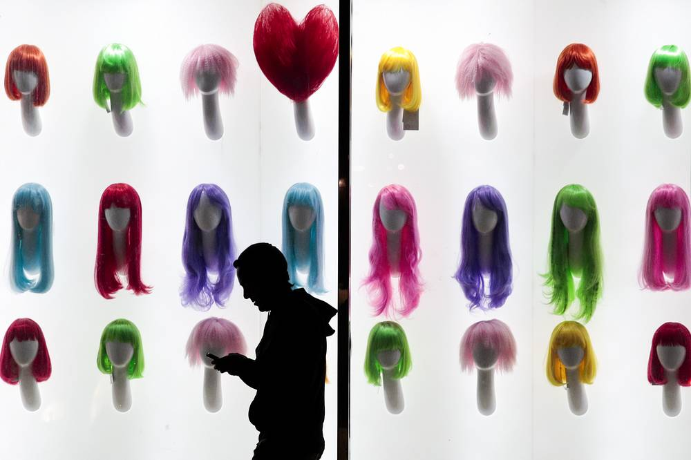 A man looks at his smartphone as he walks past colorful wigs on display in a store window in Los Angeles, USA, November 29
