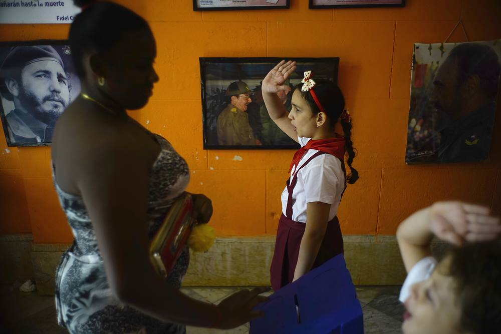Back-dropped with pictures of the late Fidel Castro and President Raul Castro a school girl and boy raise their hands to confirm a vote as a woman casts her ballot for municipal elections in Havana, Cuba, November 26