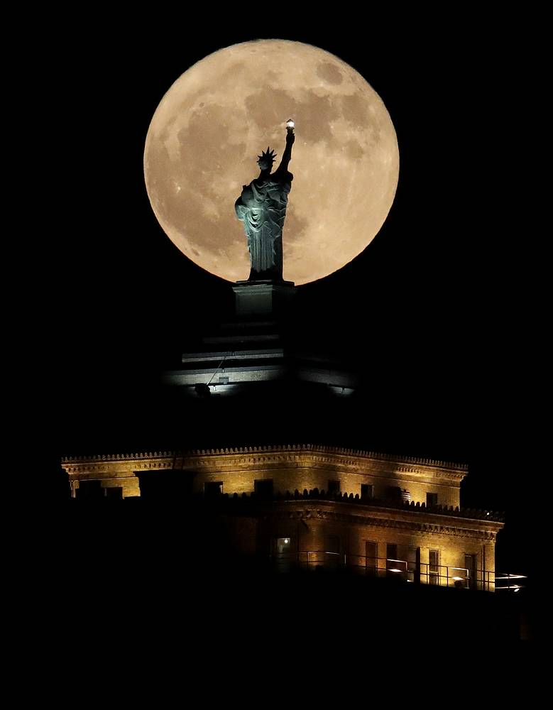 Supermoon rises in front of a replica of the Statue of Liberty sitting atop the Liberty Building in downtown Buffalo, USA. December's full moon appears bigger and brighter in the sky as it sits closer than average to Earth