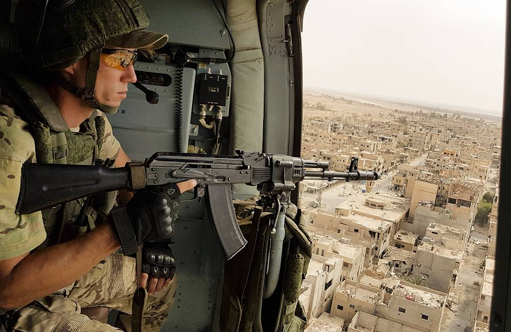A Russian soldier guards as a military helicopter flies over Palmyra, September 15, 2017