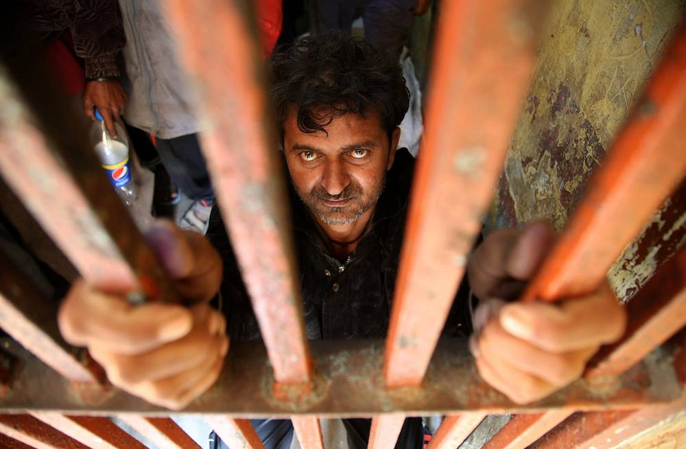 Indian fishermen who were arrested after allegedly straying into Pakistan's territorial waters, sit behind bars at a police station in Karachi, Pakistan, December 14. The two countries' maritime security forces often arrest each other's impoverished fishermen for allegedly violating the territorial waters where demarcation is not clear