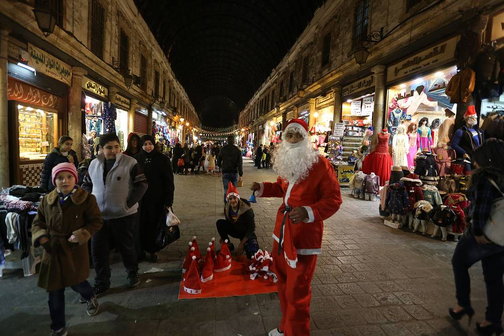 A Syrian dressed in Santa Claus clothes is seen at al-Hamidiyeh old souk in Damascus, Syria