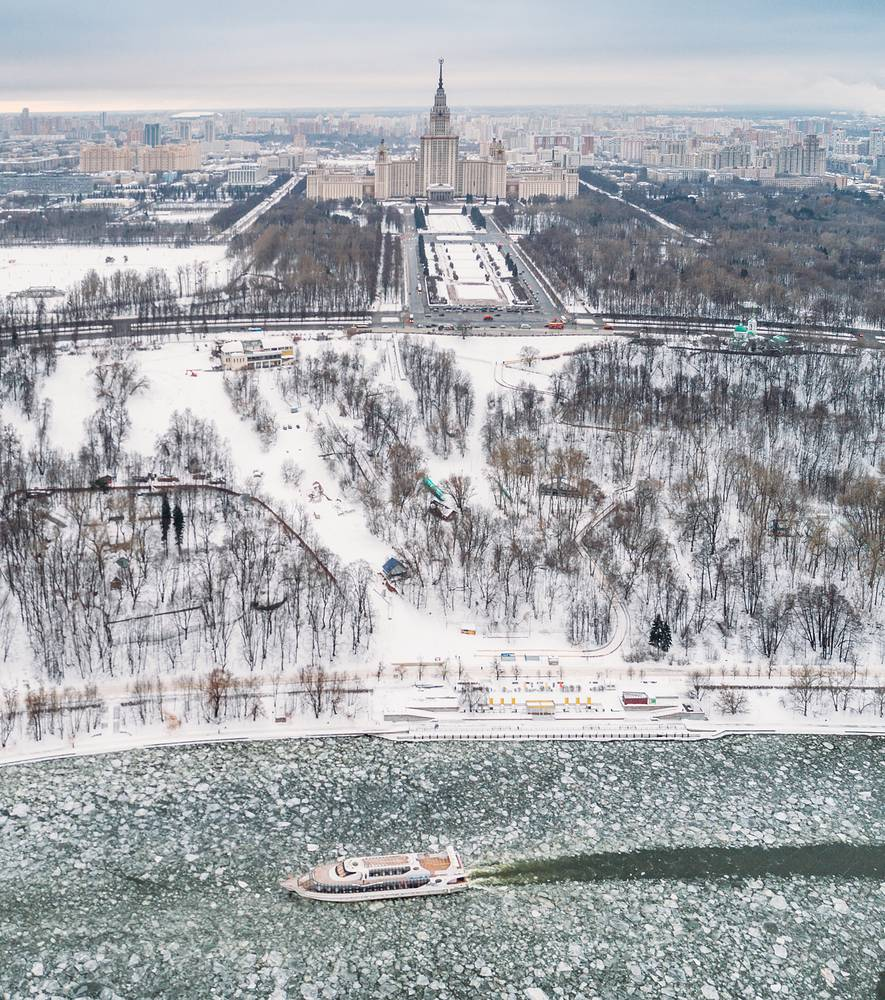 A boat making its way along the ice-covered Moskva River with Lomonosov Moscow State University in the background, February 11
