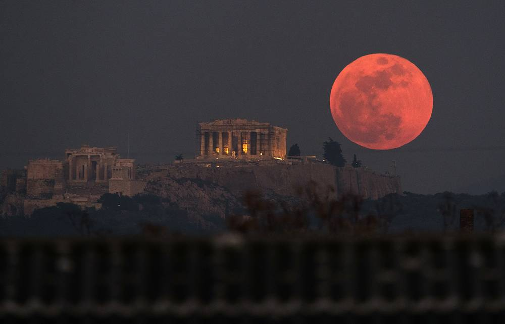 A super blue blood moon is seen behind the 2,500-year-old Parthenon temple on the Acropolis of Athens, Greece