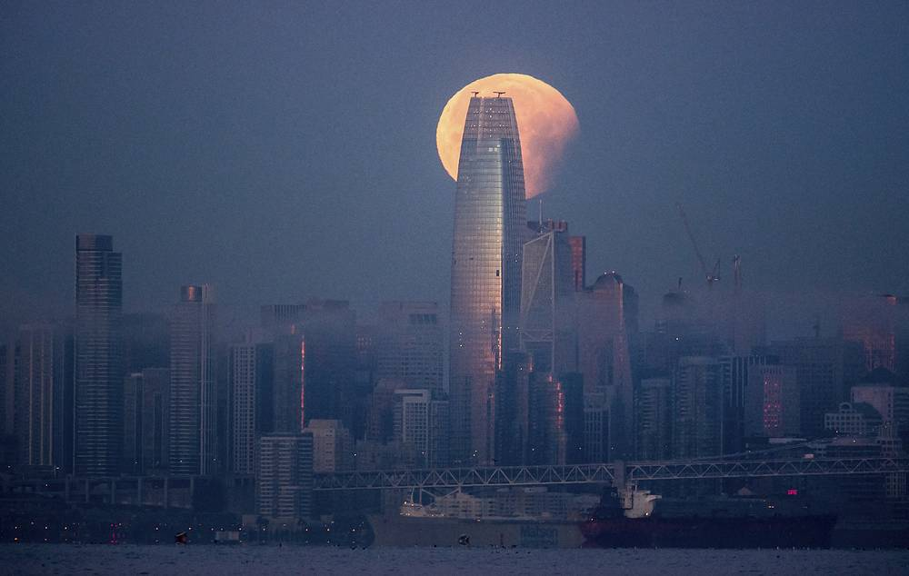 A partially-eclipsed super blue blood moon sets behind the Salesforce Tower in San Francisco, USA