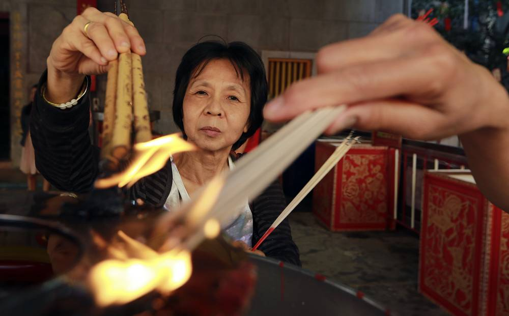Ethnic Chinese Thais burn joss sticks at the Leng Nuei Yee Chinese temple in Bangkok, Thailand