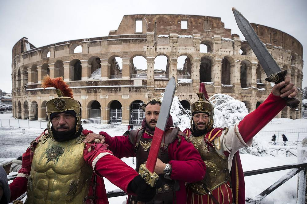 Men posing as a centurions in front of the Colosseum covered by snow during a snowfall in Rome, Italy