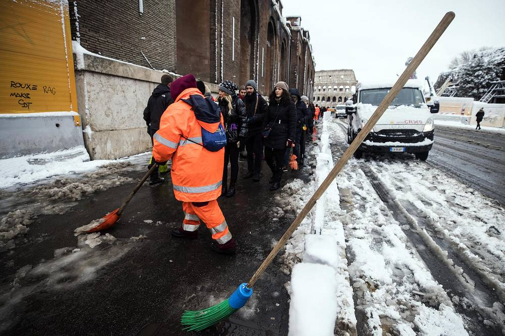 Municipal workers clear snow from a footpath in a street after heavy snowfall in Rome, Italy