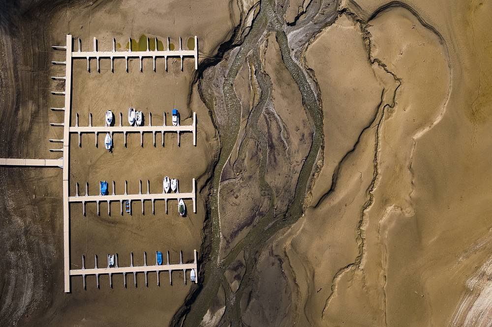 Stranded boats are pictured on the dried out shoes of the Lake of Gruyere in La Roche near Bulle, Switzerland, March 14