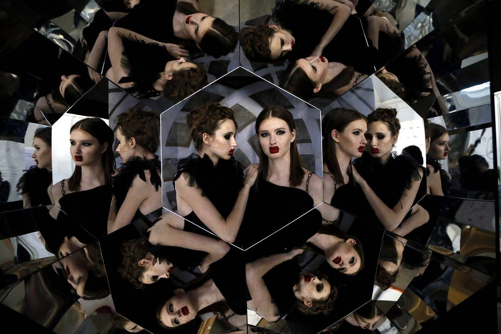 Models pose for a selfie in a hexagon mirror backstage during the Mercedes-Benz Fashion Week Russia in Moscow, Russia, March 12