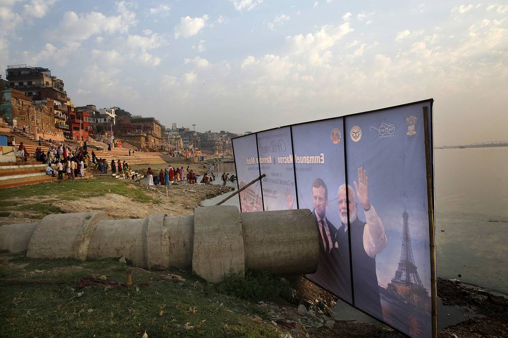 A huge banner welcoming the French President Emmanuel Macron and Indian Prime Minister Narendra Modi is placed in front of a sewage pipe that drains into the Ganges river in Varanasi, India, March 12
