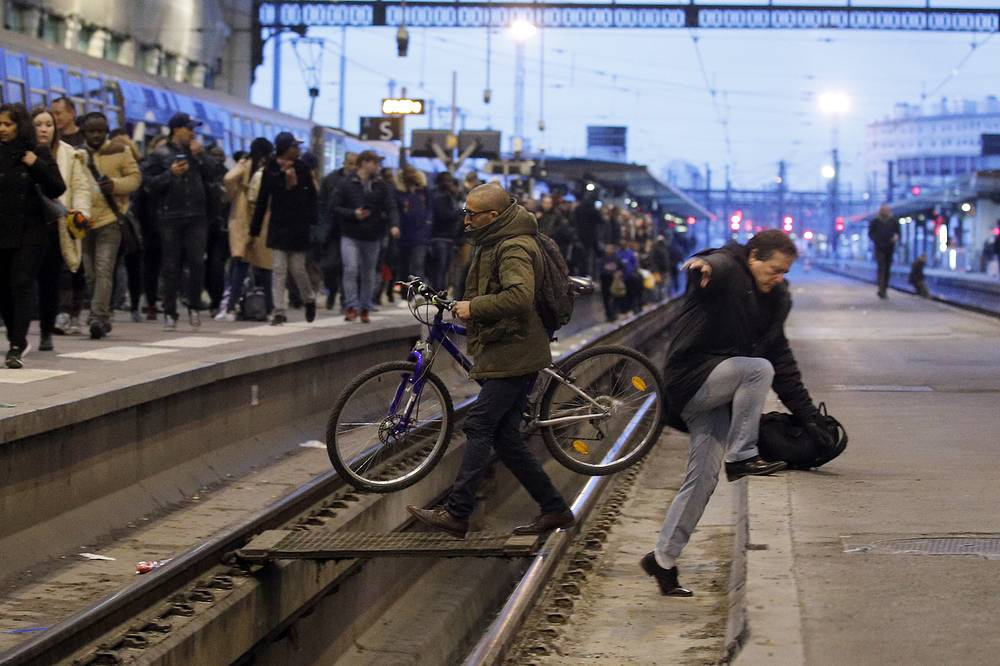 Passengers cross railroad tracks at rush hour at Gare de Lyon train station, in Paris, France, as union stage a mass strike to protest government plans to eliminate some rail worker benefits, April 3