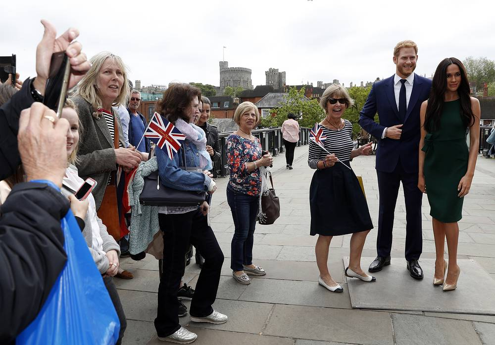 Tourists gather to take photos with waxwork figures of Britain's Prince Harry and Meghan Markle against the backdrop of Windsor Castle, in Windsor, May 16. Preparations continue in Windsor ahead of the royal wedding of Britain's Prince Harry and Meghan Markle