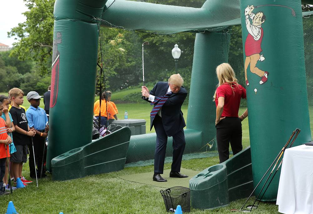 US President Donald Trump swings a golf club as young participants look on during the White House Sports and Fitness Day event on the South Lawn of the White House in Washington, May 30