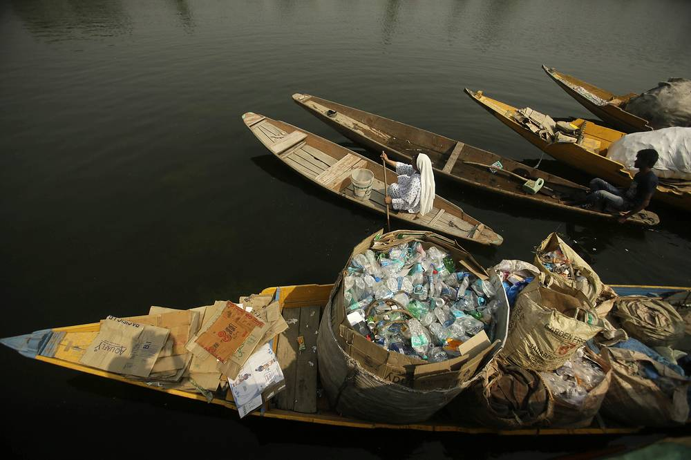 A Kashmiri woman rows her boat past another loaded with plastic bottles and other waste collected from the Dal Lake in Srinagar, Indian controlled Kashmir