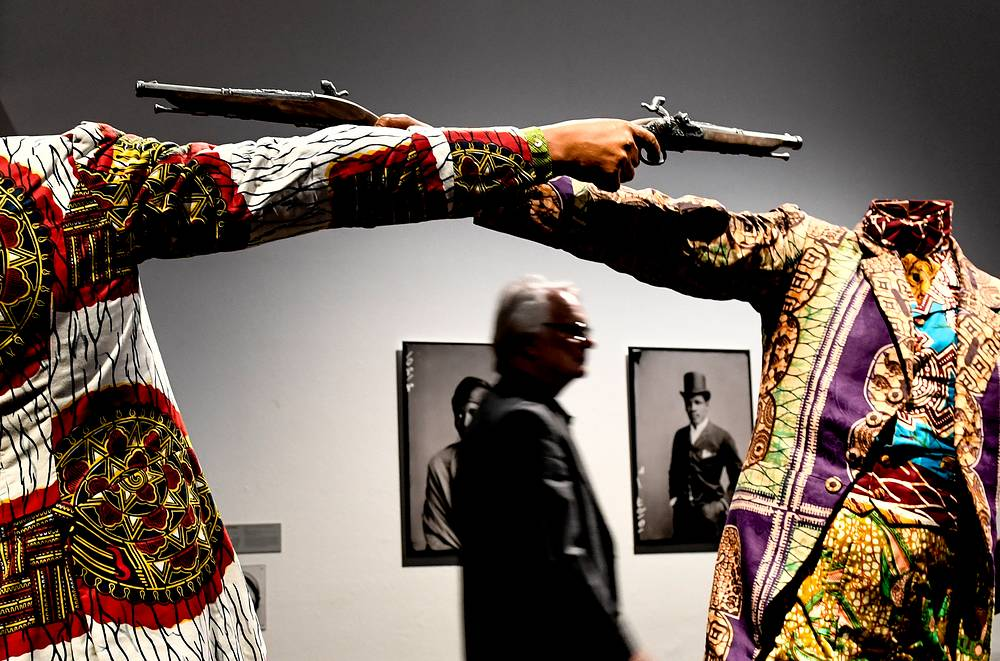 A visitor pass by artworks 'How to Blow Up Two heads at once' by Yinka Shonibare inside the exhibition 'Racism'. The Invention of Human Race ' at the German Hygiene Museum in Dresden, June 13