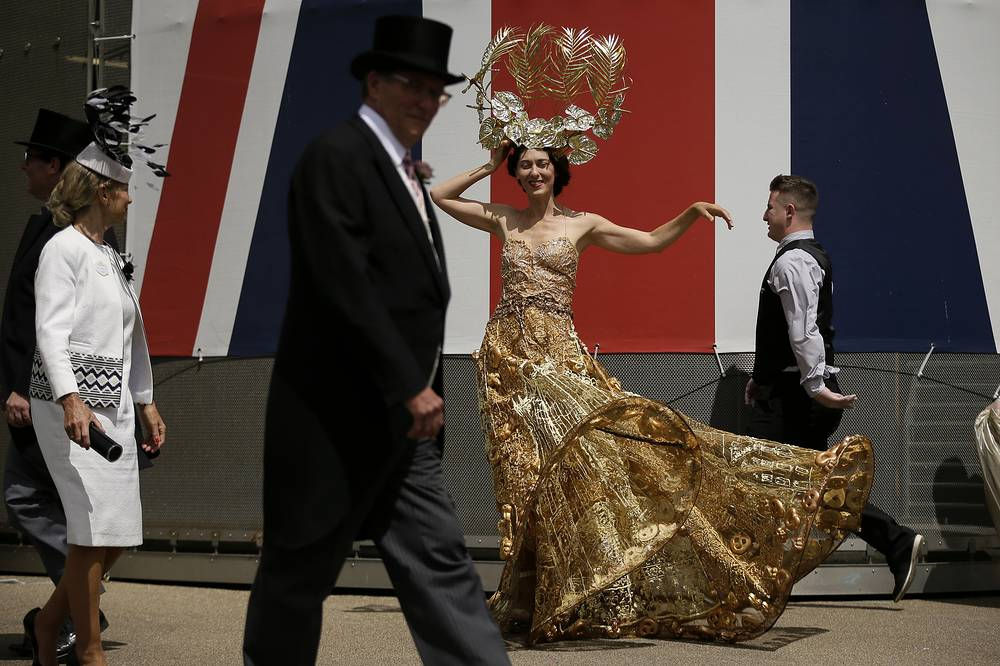 A racegoer poses for photographers on the second day of the Royal Ascot horse race meeting in Ascot, England, June 20