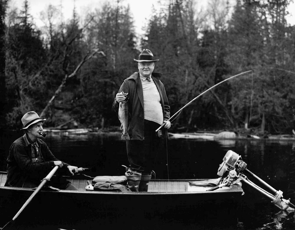 With a guide at the oars, former president Herbert Hoover displays a trout he caught while fishing in New England, 1939