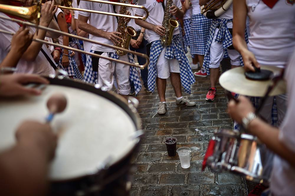 A group of musicians play with glasses of liquor at their feet, at the San Fermin Festival in Pamplona