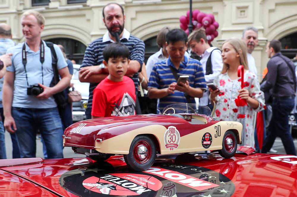 People look at a cabriolet model in Ilyinka Street